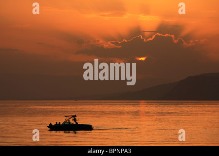 Crepuscular rays make for a dramatic sunset over Lake Geneva in Switzerland - Stock Photo