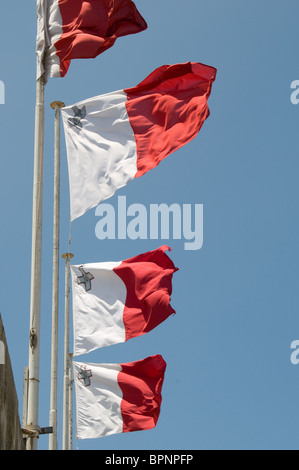 A trio of Maltese National flags fly in a stiff wind against a blue sky. - Stock Photo