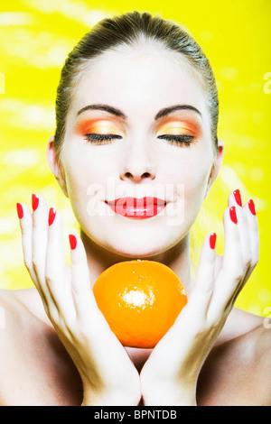 beautiful caucasian woman portrait smelling a citrus fruit pleasure smile studio on yellow background - Stock Photo