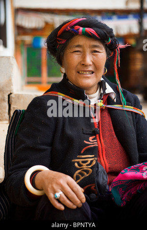 A lady dressed in traditional minority clothes rests near songzanlin tibetan monastery,shangri-la (Zhongdian) Yunnan, - Stock Photo