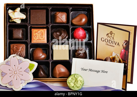 An open gift box of gourmet Godiva chocolates and truffles displayed after being unwrapped. - Stock Photo