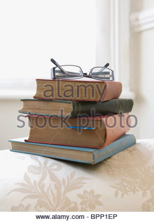 Pile of books on arm of sofa - Stock Photo