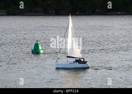 A small yacht sails past a green buoy at Devil's Point in Plymouth Sound. - Stock Photo