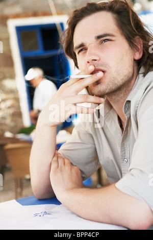 Man smoking cigaret in restaurant - Stock Photo
