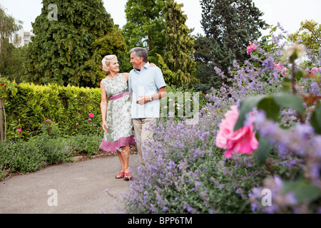 Mature couple walking in rose garden - Stock Photo