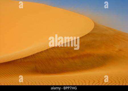 Wind blowing on a dune in the Rub al Khali or Empty Quarter, straddling Oman, Saudi Arabia, the UAE and Yemen. - Stock Photo