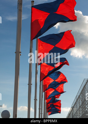 View looking up at colourful flags flying in the wind - Stock Photo