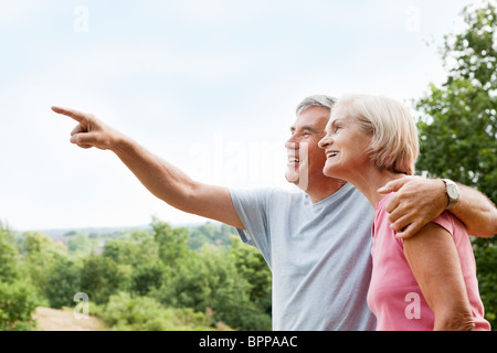 Mature man embracing woman points away - Stock Photo