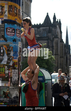 Couple hanging posters promoting a Fringe show in the Edinburgh Festival, Scotland. - Stock Photo