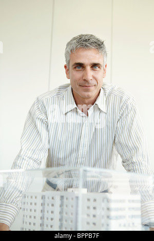 Man standing next to architectural model - Stock Photo
