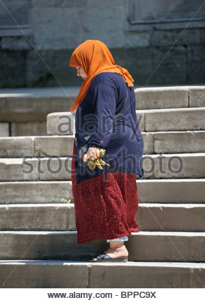 Old Turkish woman wearing headscarf visiting a Mosque in Sultanahmet Istanbul Turkey - Stock Photo
