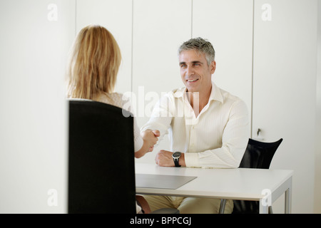 Older man and woman shaking hands - Stock Photo