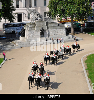 Hyde Park Corner Household Cavalry passing the Royal Artillery Memorial - Stock Photo