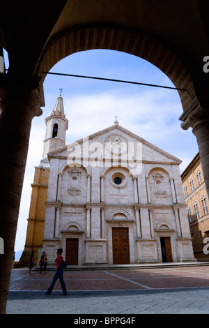 ITALY, Tuscany, Pienza, Val D'Orcia The Duomo in Piazza Pio II seen through an arch with tourists walking in the - Stock Photo