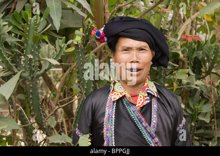 Photograph of a Lu minority wearing traditional clothing with her teeth blackened woman in front of a cactus - Stock Photo