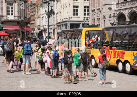 Markt, Bruges, Belgium, Europe. Group of children on a school trip by city tour buses in the square - Stock Photo