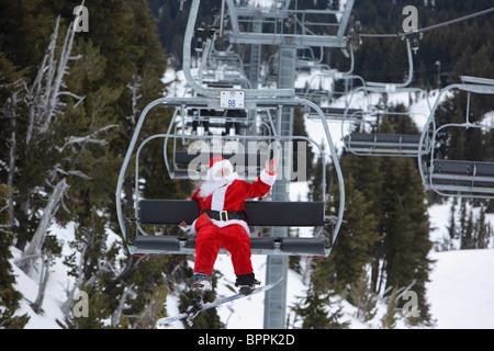 Santa claus with snowboard on ski lift - Stock Photo