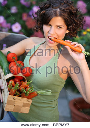 young brunette woman carrying basket with vegetables - Stock Photo
