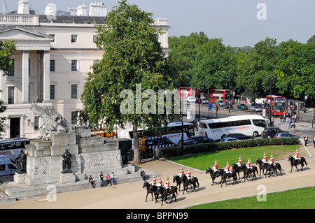 Hyde Park Corner Household Cavalry passing the Royal Artillery Memorial and the Lanesborough Hotel - Stock Photo