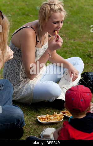 girl sat on grass eating chips at a country fair - Stock Photo