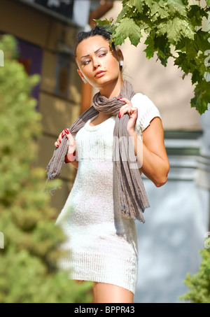 Beautiful young woman in autumnal city in white dress - Stock Photo