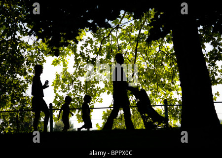 The outline of a family strolling in the Napoleon III Park in Vichy (France). Woman and man with children. - Stock Photo