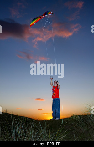 'Children at Play' _ Young boy flying Kite at Sunset on Southport Beach, Merseyside, England, UK - Stock Photo