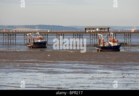 Two fishing boats beached at low tide near the pier in Southend on Sea in Essex.  Photo by Gordon Scammell - Stock Photo