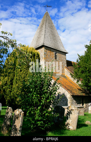 St Peter church in Rodmell with its square tower, pyramidal cap and flint walls typical in Essex, England - Stock Photo