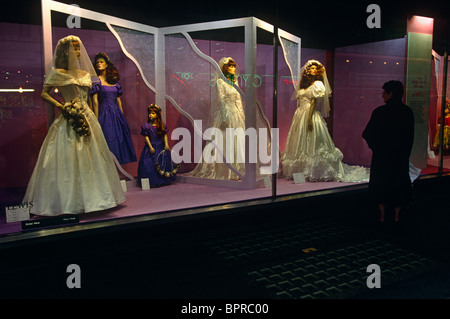 Bridal wedding dresses are watched by shopper on shop window mannequins in London's John Lewis department store. - Stock Photo