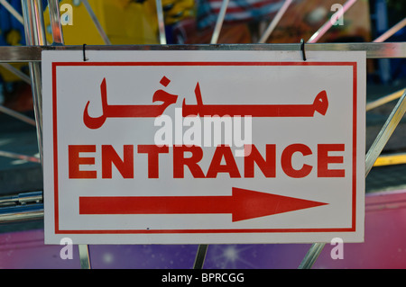 Bilingual sign in English and Arabic saying 'Entrance' with an arrow - Stock Photo