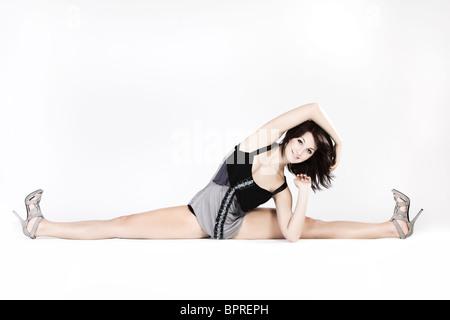 Young flexible dancer doing leg-splits isolated on white - Stock Photo
