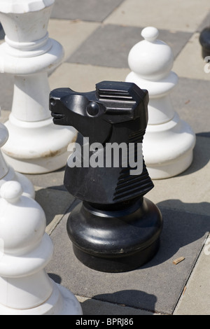 Close-up of a chess pieces on giant chess board outdoors - Stock Photo
