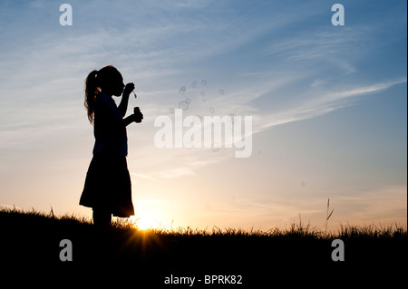 Silhouette of a Young girl blowing bubbles at sunset. - Stock Photo