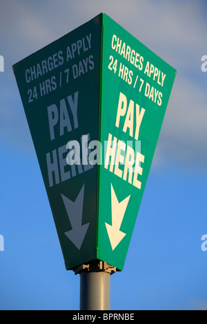 Sign post in a car park indicating where to pay and that charges apply 24/7. - Stock Photo