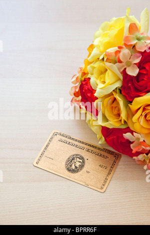 American Express gold card next to flowers - Stock Photo