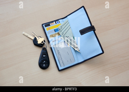 wallet with money and cards and car keys on table - Stock Photo