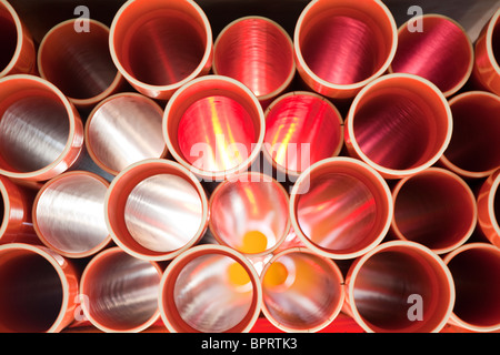 Brown PVC pipes stacked in construction site - Stock Photo