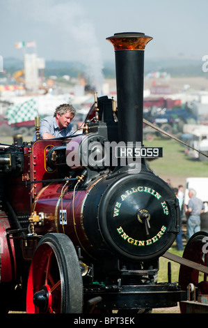 Vintage Steam traction engine powering a wood saw at Great Dorset steam fair in England - Stock Photo