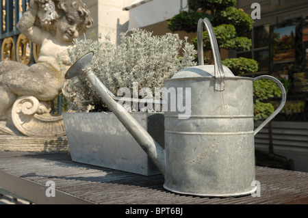 A traditional galvanised metal watering can on a bench with an ornament and gardens in the background. - Stock Photo