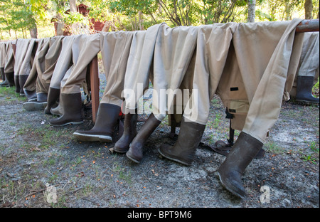 Fishing gaiters lined up on a railing - Stock Photo