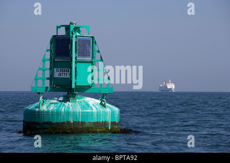 Belfast lough cloghan point maritime navigation buoy warning marker with ferry in the background - Stock Photo
