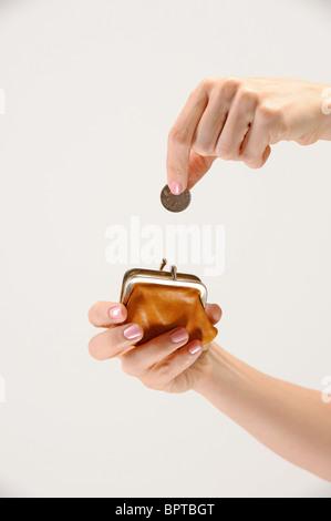 woman puts quarter into coin purse - Stock Photo