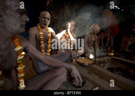 Holy Sadhus men smoking hash at early morning in preparation for the Kumbh Mela festival Haridwar, Uttarakhand, - Stock Photo