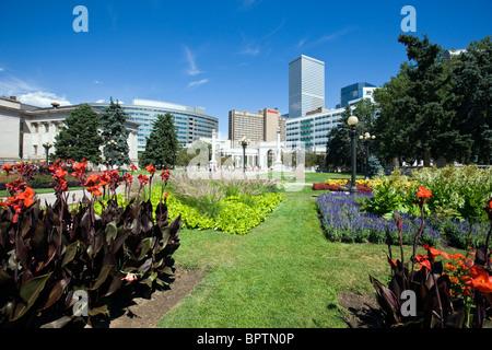Lush flower gardens, Voorhees Memorial Seal Pond, modern city skyline, Civic Center Park, Denver, Colorado, USA - Stock Photo
