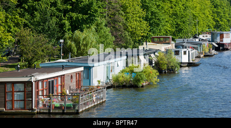 House boats in Amsterdam on the river Amstel, with floating gardens and decks or balconies. - Stock Photo