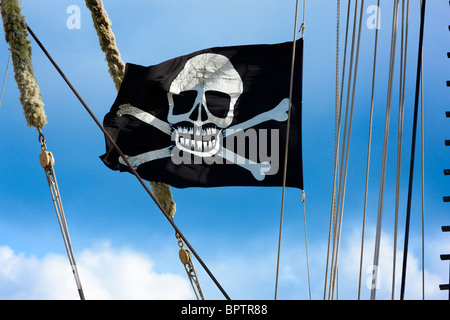Skull and crossbones, Jolly Roger, a pirates' flag flying on a historic tall ship - Stock Photo