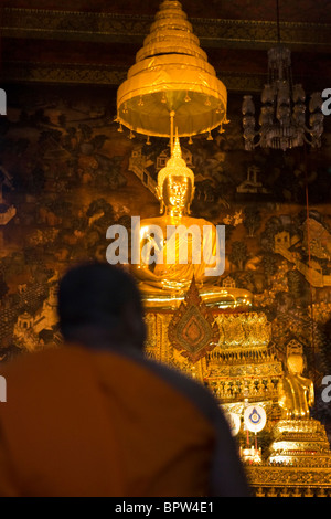 A monk kneels in front of a Buddha statue in Wat Po, Grand Palace, Bangkok, Thailand. Indochina. Southeast Asia. - Stock Photo