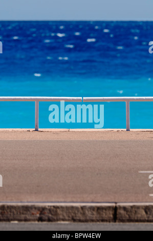 Footpath and railings in front of a bright blue sea - Stock Photo