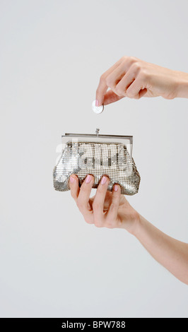 woman's hands put money into silver coin purse - Stock Photo